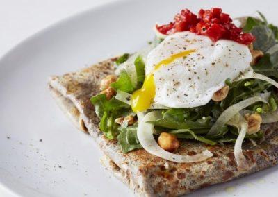 Buchweizen Crepe gefüllt mit Speck und Gruyere sowie belegt mit einem Rucola-Fenchel-Salat, pochiertem Ei und Haselnüssen