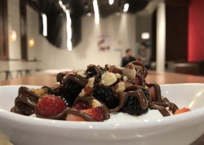 Panzanella Früchteschale mit Naturjoghurt garniert mit Beeren, Orangenschale, Kuchencroutons, geröstete Haselnüsse und Nutella